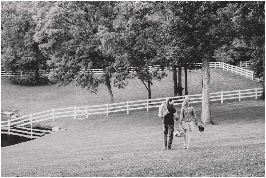 A St Louis couple sharing a champagne picnic at their outdoor, rustic engagement session